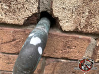 A gap of roughly a quarter inch around a gas pipe where it passes through a brick wall needs to be sealed to keep mice out of a house in Atlanta