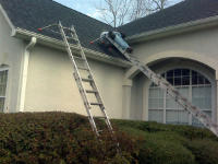 Man opn a ladder on a roof in Atlanta performing squirrel exclusion work