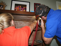 Two technicians treating a dresser for bed bugs