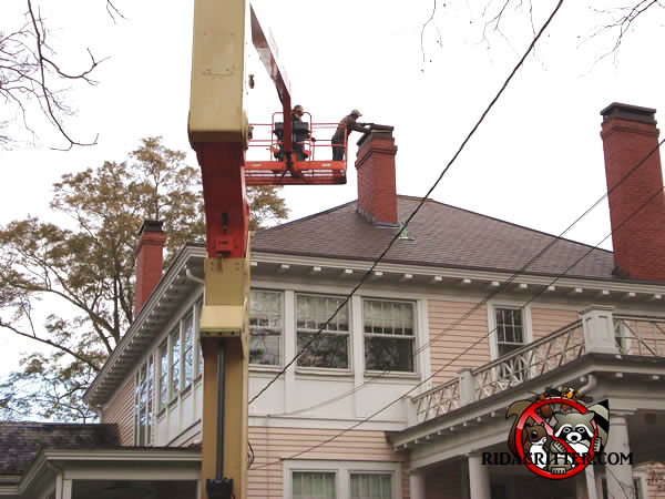 Men On A Platform Lift Installing Chimney Cap House To Keep Animals Out